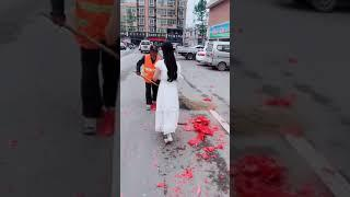 Bride hands out hongbao to street cleaners after blowing up fireworks on the road